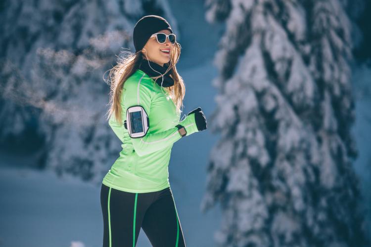 Sport d'hiver et vue : femme portant des lunettes en montagne pour se protéger des UV du soleil, de la réverbération et de l'éblouissement dû au soleil.