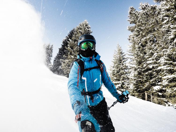 Sport d'hiver et vue : homme faisant du ski et portant un masque de ski au dessus de ses lunettes de vue, pour protéger ses yeux du soleil et de ses UV