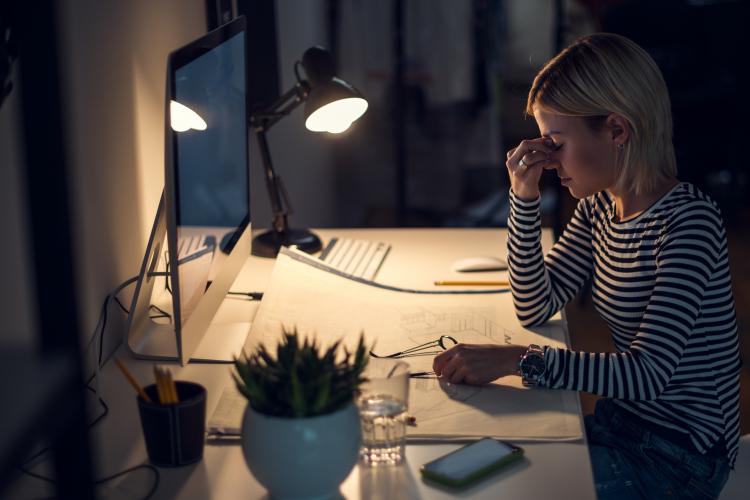 Fatigue oculaire : femme fatiguée qui travaille face à un écran, avec peu de lumière et qui ressent des symptômes de fatigue visuelle