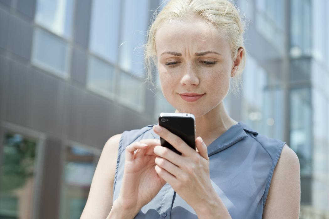 Jeune femme qui essaye ses futurs verres de lunettes Essilor en ligne sur son smartphone, grâce à la technologie d'essayage virtuel FittingBox.