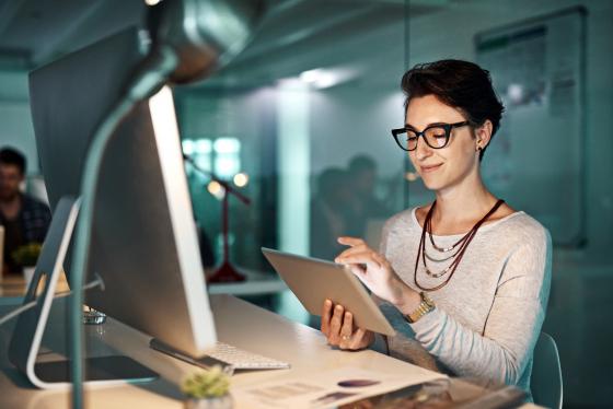 Fatigue oculaire : jeune femme portant des lunettes au bureau et adoptant la bonne posture de travail, face à son écran d'ordinateur.