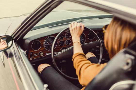 Vue et conduite : femme au volant d'une voiture, portant des lunettes de soleil pour se protéger de la lumière aveuglante (éblouissement).