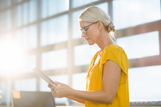Fatigue oculaire : femme portant des lunettes de vue et utilisant une tablette tactile