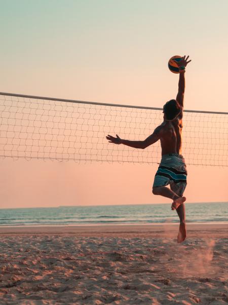Sport de balle et vue : homme jouant au beach volleyball sur la plage au coucher de soleil